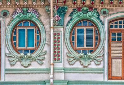 Round plaster work and ornate window frames in the 1920's Shophouse style. Fruits and flowers decorate the tops of the window frames.