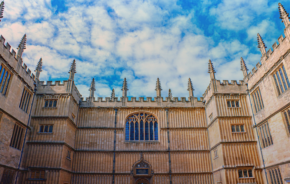 Looking up towards a blue sky and the walls and roof of the Old Schools Building. Bodleian Library.